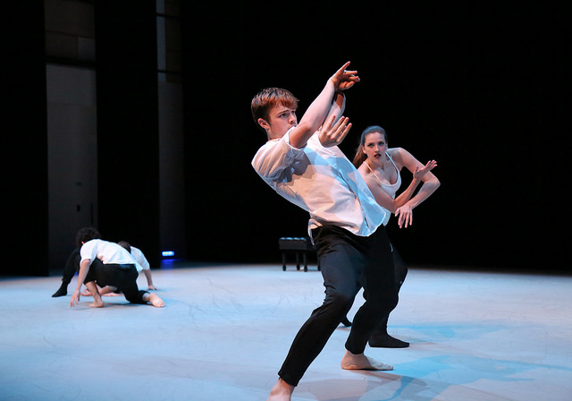 Three dancers in white shirts and black pants dancing onstage