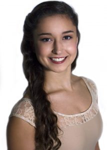 A portrait of a girl in a pink leotard with her hair down, smiling against a white backdrop.