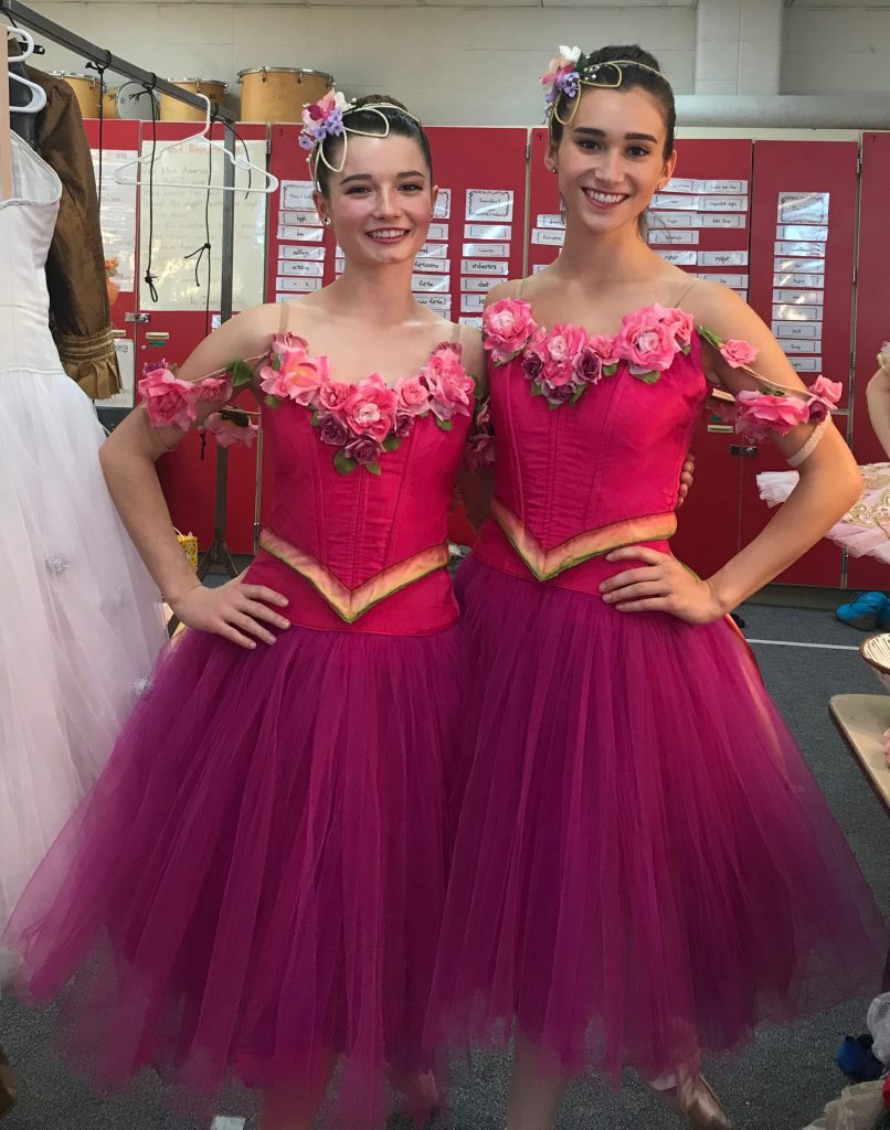 two women standing with hands on their hips wearing pink costumes from The Nutcracker