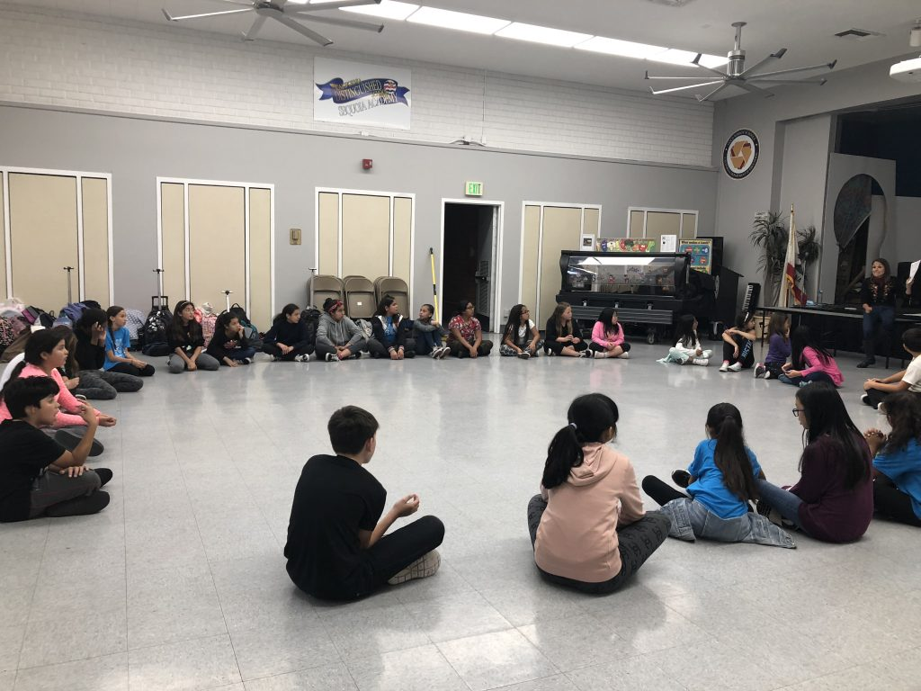 Elementary schoolers sit in a large circle on the classroom floor.