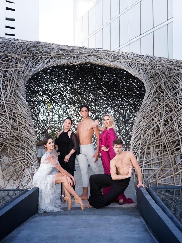 Five dancers posing in front of sculpture.
