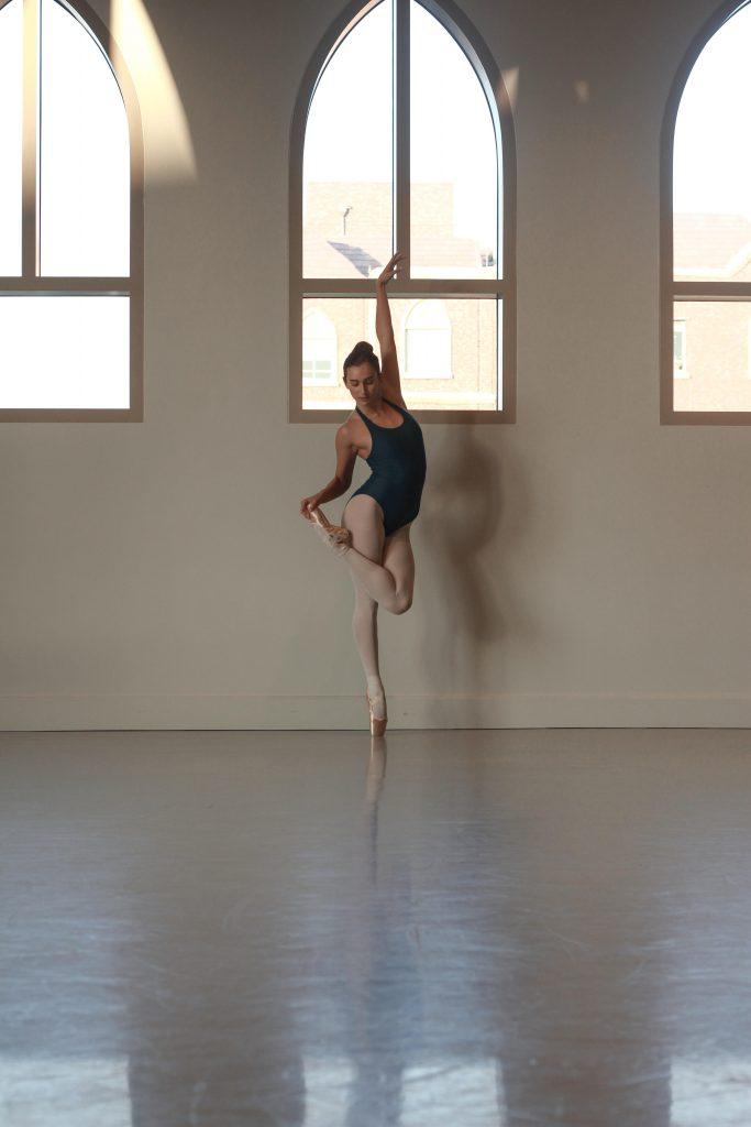 Dancer on pointe holding foot, wearing blue leotard.