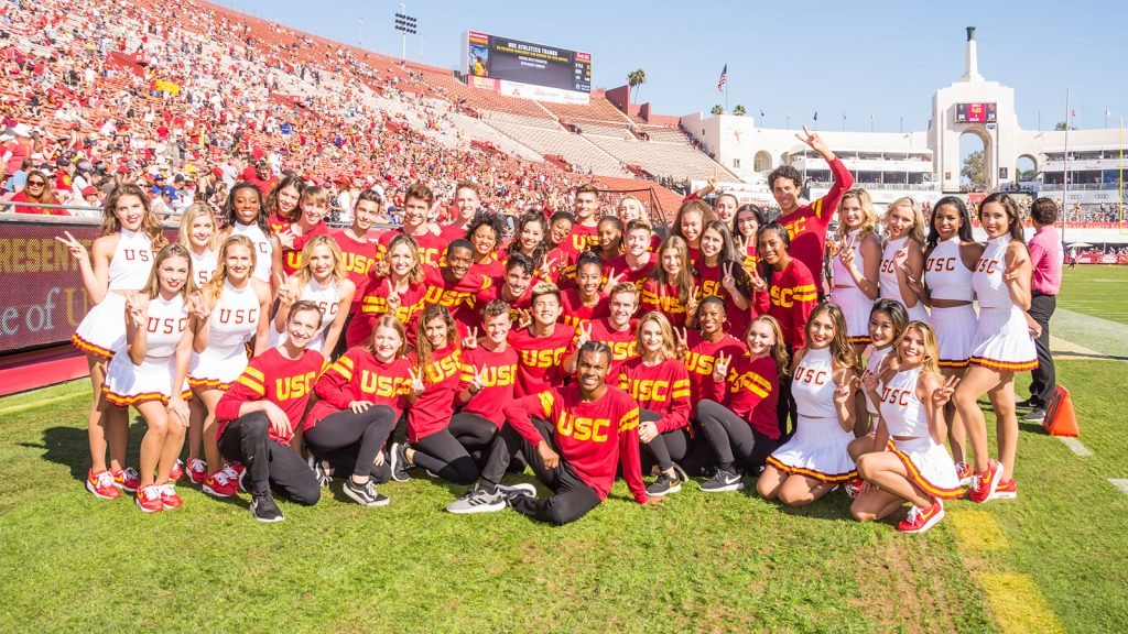 Students in red USC shirts on football field