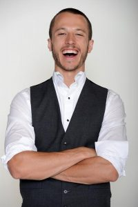 man with arms crossed and laughing wearing white button down and gray vest